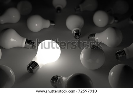 One lit light bulb amongst other broken light bulbs - shallow depth of field - stock photo