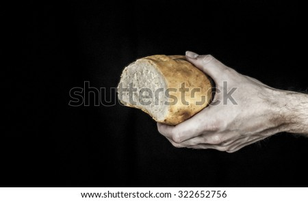 One male hand holding a loaf of bread isolated on a black background