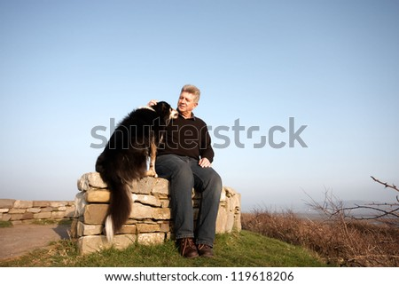 One man and his dog sitting on a wall - stock photo