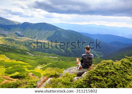 one man and loyal friend dog watching the beautiful pensive dreamy magical mountain landscape. Time for reflection. Harmony with yourself.. Series of photos - stock photo