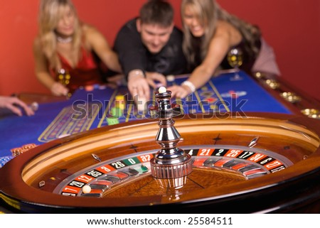 One man and two girls playing roulette - stock photo