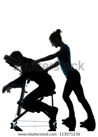 one man and woman perfoming chair back massage in silhouette studio on white background - stock photo