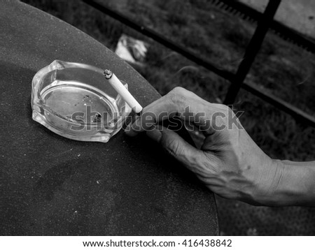 One man holding a cigarette in his hand on the table with black white tone - stock photo