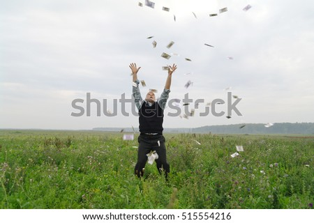 One man in the field at nature, catches the money flying from the sky above