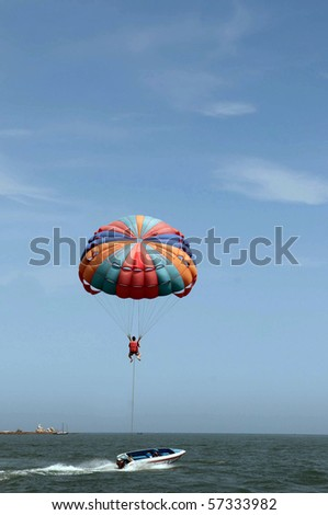One man is para-sailing over the clean sea. - stock photo