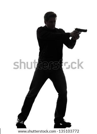 one man killer policeman aiming gun standing silhouette studio white background - stock photo