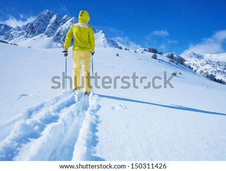 One man walking with ski over the snow land to the mountain view from back - stock photo