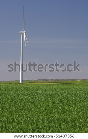 one modern windmill in a meadow with blue sky - stock photo