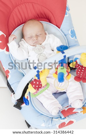 one month old baby girl sleeping in baby''s chair - stock photo