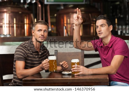 One more beer please! Two friends drinking beer at the pub while one of them asking a waiter. - stock photo
