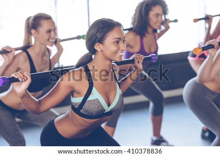 One more squat. Beautiful young women with perfect bodies in sportswear exercising with barre while standing in front of window at gym - stock photo