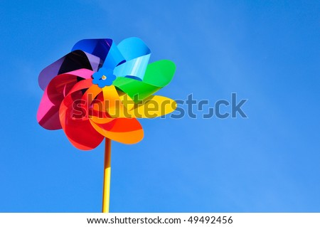 One multi-coloured windmill toy. Blue background. - stock photo