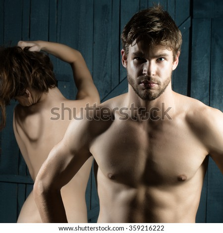One muscular sexy strong young bearded macho man with beautiful body and bare chest standing indoor looking forward and naked woman holding long hair on blurred background, square picture - stock photo