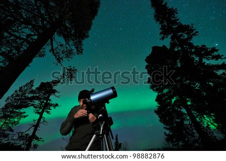 One night man watching northern sky, aurora behind. - stock photo