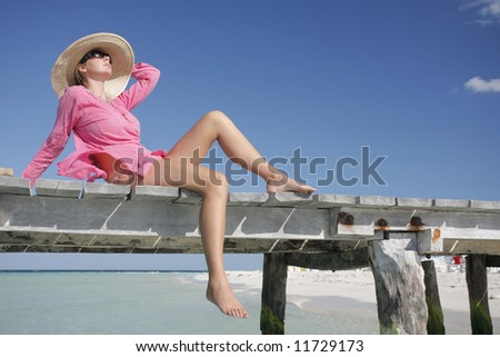 One of a large series. Woman in pink kaftan sunbathing on a wooden jetty. - stock photo