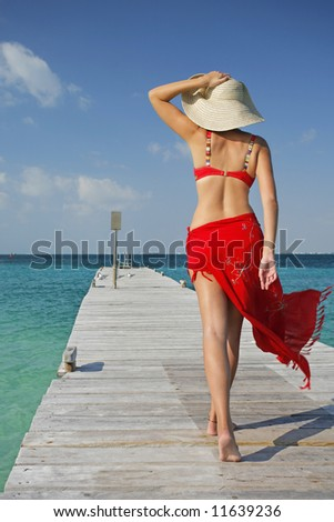 One of a large series. Woman in red bikini walking down a tropical jetty