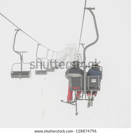 One of chair lifts in a ski resort of a valley of Zillertal in the fog - Mayrhofen region, Austria - stock photo