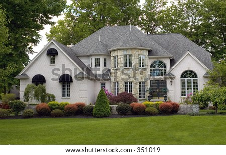 One of he most beautiful house I have seen. Reminds me of a castle with the stone round front architecture and the landscaping is immaculate. Just waiting for a princess to walk out. - stock photo