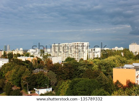One of modern suburbs of Warsaw, surrounded with trees and with blue cloudy sky on the background.