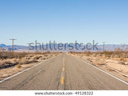 One of the many empty desert roads in Mojave National Monument, California. - stock photo