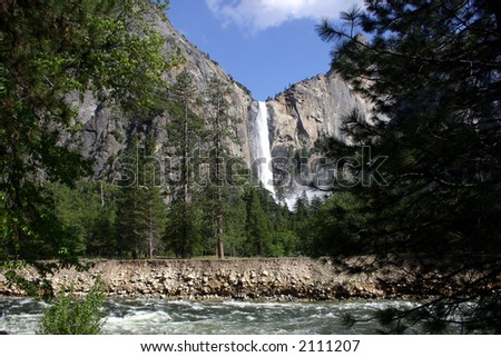 One of the many magestic waterfalls in Yosemite National Park. The Merced River in the foreground. - stock photo