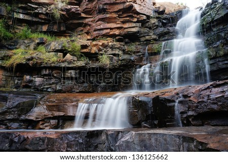 One of the many waterfalls with rock pools in the Kimberley, the last frontier in Western Australia. - stock photo