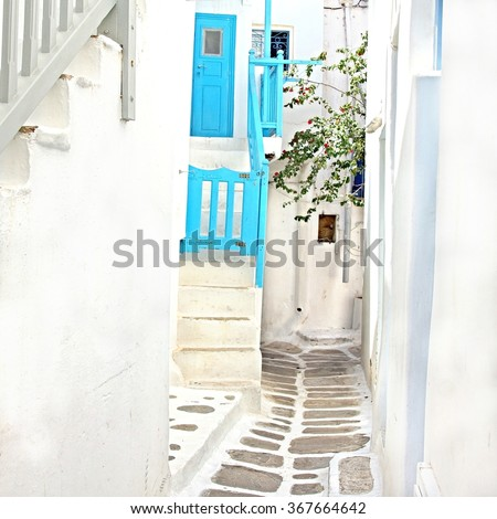 One of the many white washed picturesque sunny cobble stone streets at the town of Mykonos, Greece