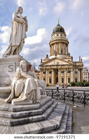 One of the most beautiful squares in Berlin, the Gendarmenmarkt, showing a marble statue of German poet Friedrich Schiller and the French Cathedral in the background. - stock photo
