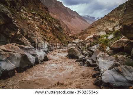 One of the tributaries of the Hunza river flowing through the beautiful mountain valley in the northern part of the Karakorum mountains in Pakistan - stock photo