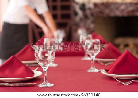 One of waiters is serving dinner place in a restaurant - stock photo