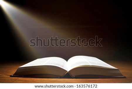 One old book on wooden table with ray of light