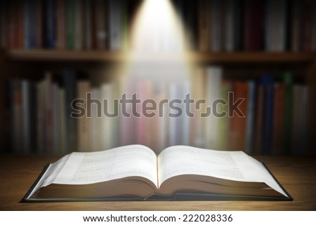One old book on wooden table with ray of light  - stock photo