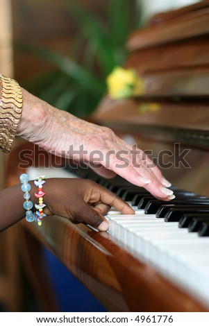 One older white hand and one younger black hand playing the piano - stock photo