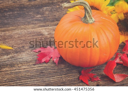 one orange pumpkin with sunflowers and fall leaves on wooden textured table, retro toned