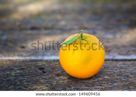 One orange with leaf on wooden table. Also available in vertical format.