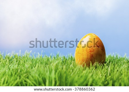 One painted yellow easter egg in grass with blue background. - stock photo