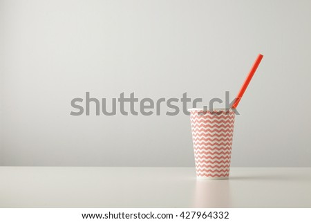 one paper cup decorated with red line pattern and with drinking straw inside isolated on white table Place for your text above - stock photo