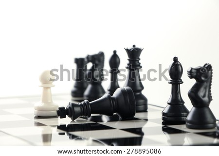 One pawn defeat the black army with the black king laying on the chess board. - stock photo