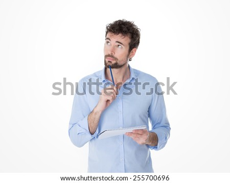 one pensive guy looking for words for his notes - stock photo
