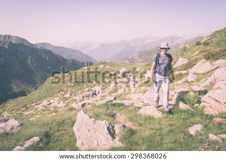 One person hiking uphill on footpath in the italian Alps with panoramic view on the mountains. Summer adventures on the Alps. Marsala toned image, vintage filter style, desaturated, vignetting added. - stock photo
