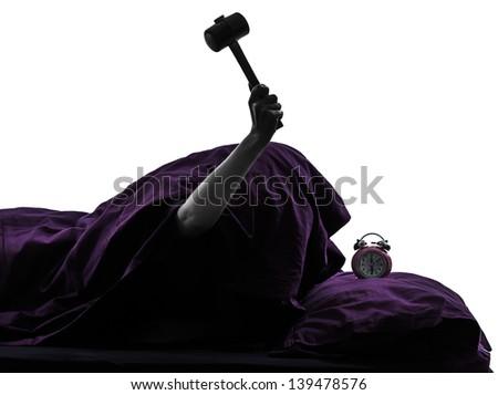 one person smashing alarm clock in bed waking up smashing alarm clock silhouette studio on white background - stock photo