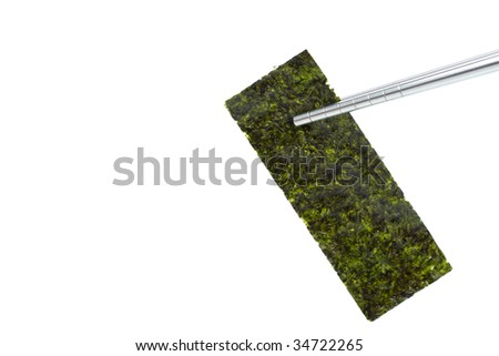 One piece of seasoned dried seaweed held up with steel chopsticks, isolated on white with copyspace - stock photo