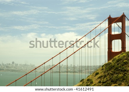 One pillar of Golden Gate Bridge with suspension cables and San Francisco in the background