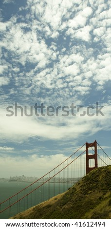 One pillar of Golden Gate Bridge with suspension cables, San Francisco in the background and blue skies with many small clouds - stock photo