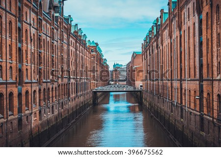 One point perspective view on canal and bridges between two long rows of old brick buildings
