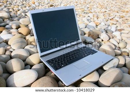 One portable computer on a stone background