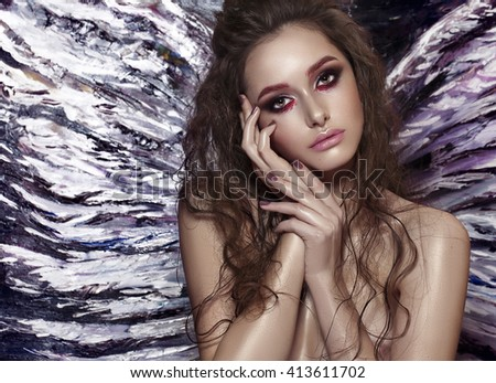 One pretty tender dreaming young fashionable woman with long curly hair bright makeup and with angel wing behind