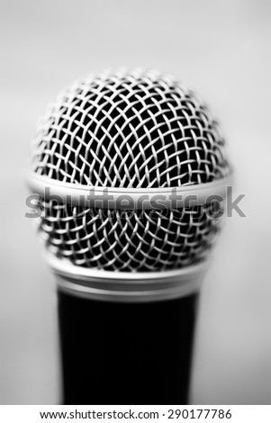One professional microphone in black with focus on head of metal wire gauze on blur grey background closeup, vertical picture - stock photo