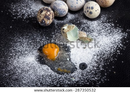 One quail egg broken into flour on black background, soft focus