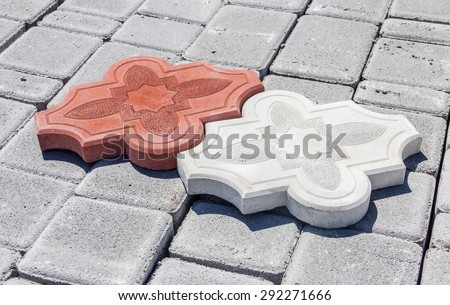 One red and one white concrete curly interlocking pavement tiles with ornament on the surface of another gray pavement tiles on depot  - stock photo